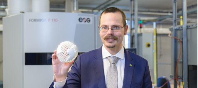 Max Andersson håller upp en 3D-printad jordglob