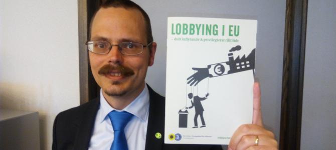 """Max Andersson håller upp broschyren """"Lobbying i EU - dolt inflytande och priviligierat tillträde""""."""